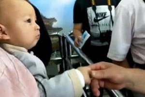 一岁宝宝跟妈妈在车站等车忽然像观察似的不断跟人握手好心爱